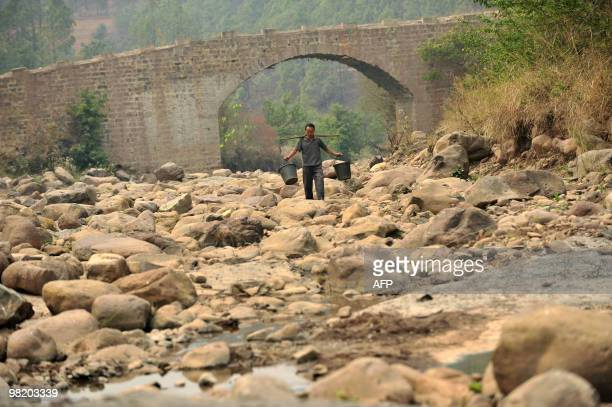 Chinese man makes his way along a dried up river bed to fetch water from a small remaining pool of water in Xinping, in southwest China's Yunnan...