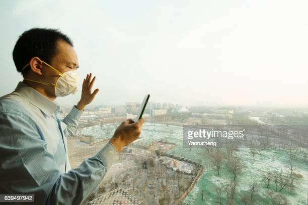 Chinese man making a call,wearing  mask against air pollution