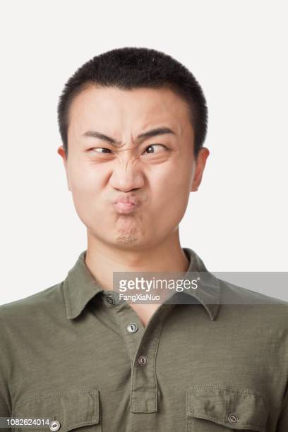 chinese man making a face - sour taste stock pictures, royalty-free photos & images