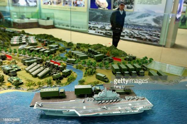 """Chinese man passes the model of China's first aircraft carrier as visiting an exhibition entitled """"Scientific Development and Splendid Achievements""""..."""