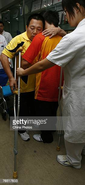 Chinese man Peng Shuilin whose body was severed in half in a traffic accident stands up from a wheelchair with the help of relatives and doctors as...
