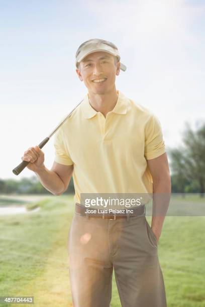 Chinese man playing golf on course