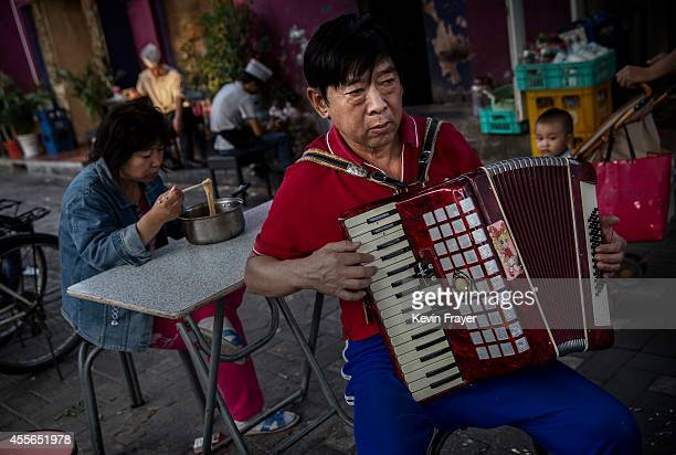 Chinese man plays accordion in the street in a residential neighborhood on September 18, 2014 in central Beijing, China.