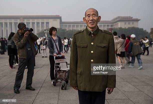 Chinese man poses in front of the Great Hall of the People in Tiananmen Square during a polluted morning on October 17 2015 in Beijing China As a...