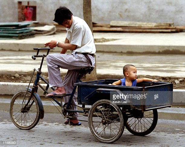 Chinese man pulls his child on a tricyle July 24 2002 in Beijing China US government officials announced July 22 2002 that they will withhold $34...
