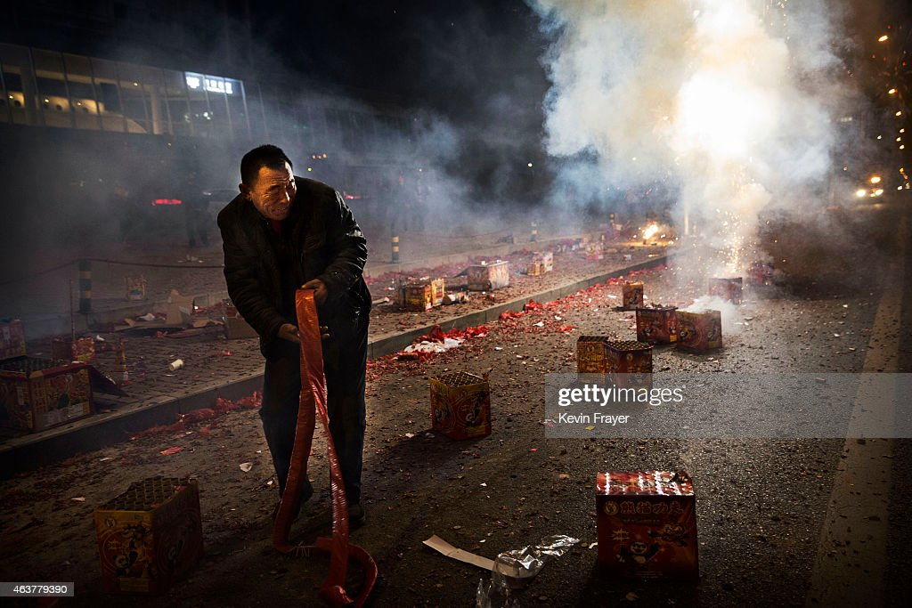 A Chinese man reacts as firecrackers he lit explode during celebrations of the Lunar New early on February 19, 2015 in Beijing, China.The Chinese Lunar New Year of Sheep also known as the Spring Festival, which is based on the Lunisolar Chinese calendar, is celebrated from the first day of the first month of the lunar year and ends with Lantern Festival on the Fifteenth day.