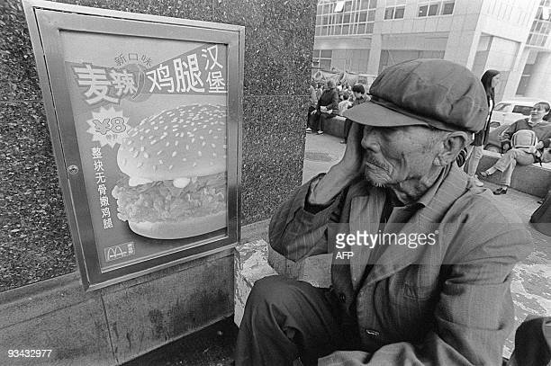 A Chinese man rests in front of a McDonald's restaurant in October 1999 in Beijing AFP PHOTO MAXIMILIEN LAMY