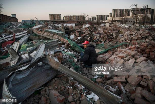 Chinese man scavenges useable items from the rubble of buildings demolished by authorities in an area that used to have migrant housing and a...