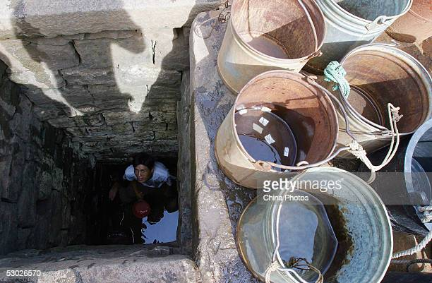 A Chinese man scoops water from a almost dried well on June 2 2005 in Leizhou of western Guangdong Province southern China According to Guangdong...