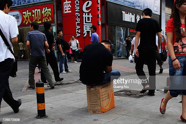 A Chinese man sits on a box of computer accessories in front of Zhongguancun ePlaza on August 26 2011 in Beijing China Zhongguancun known as 'China's...
