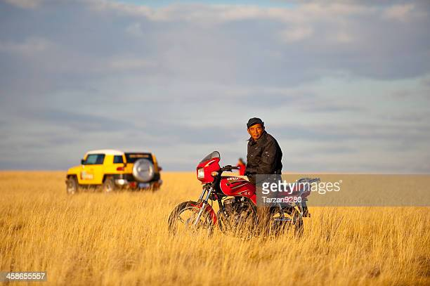 chinese man sitting on motor bike at sunset moment - agricultural occupation stock pictures, royalty-free photos & images