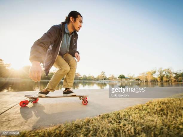 Chinese man skateboarding in park