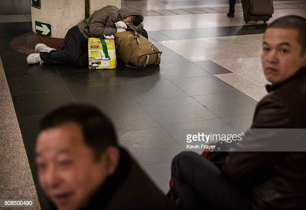 Chinese man sleeps as other travellers wait at a railway station on February 4 2016 in Beijing China Millions of Chinese are heading home for the...