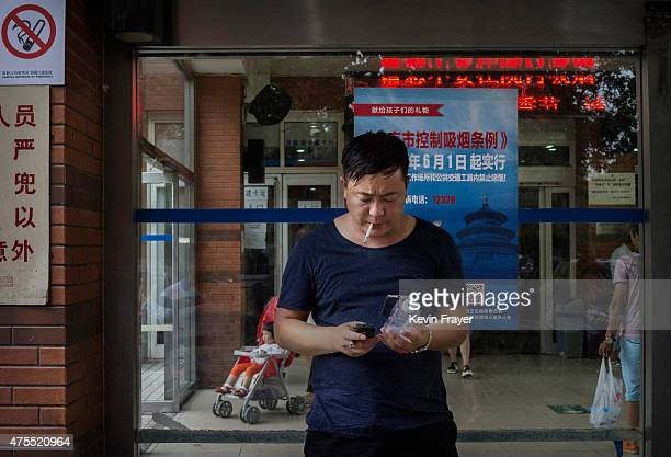 Chinese man smokes a cigarette in front of a poster notifying people of tough new antismoking laws in a prohibited area at a children's hospital on...
