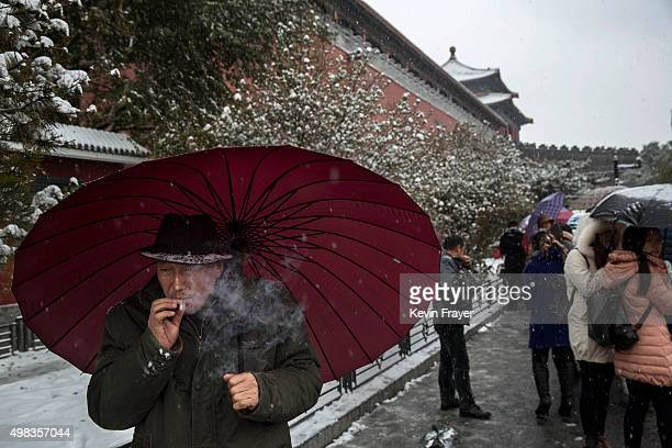 Chinese man smokes as he shields himself under an umbrella from the snow during a snowfall on November 22 2014 outside the Forbidden City in Beijing...