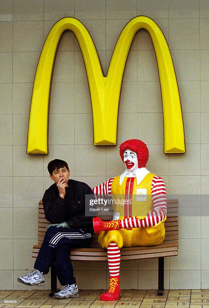 A Chinese man smokes outside a McDonalds restaurant January 25, 2002 in Beijing. China is thought to have more than 300 million smokers.