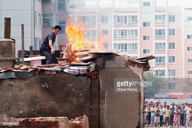 Chinese man standing on his roof hurls a Molotov cocktail at law enforcement officers to protest about his home from being demolished on July 14,...