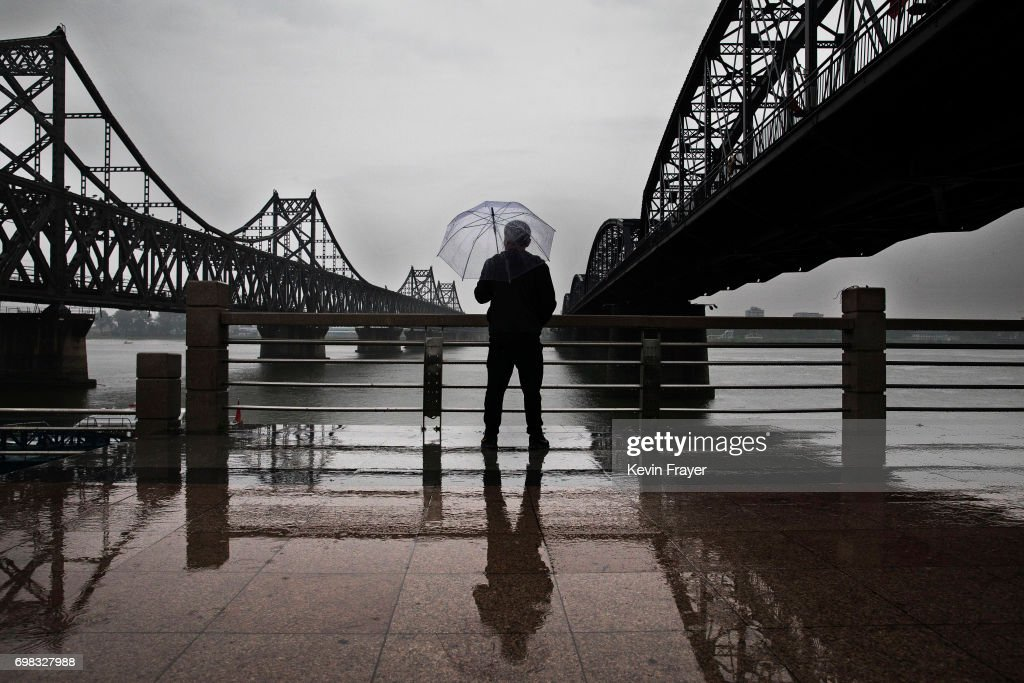 A Chinese man stands in the rain between 'Friendship Bridge', left, and 'Broken Bridge', right, as he looks across the Yalu river from the border city of Dandong, Liaoning province, northern China towards the city of Sinuiju, North Korea on May 23, 2017 in Dandong, China. China has long been North Korea's main ally and trading partner, but relations are increasingly strained by continued missile testing and provocations by the regime of Kim Jong Un. The North is almost entirely dependent on trade with China to feeds its impoverished economy, yet it has ignored calls by the international community to halt its nuclear and ballistic missile weapons programs. At least three-quarters of trade between the two nations flows through points along its 880-mile long shared border, a divide that reveals stark contrasts in development. Cities such as Dandong boast high-rise buildings and advanced infrastructure, and the Friendship Bridge serves as the conduit for the bulk of trade. From hired boats along the Yalu river, Chinese tourists peer into the reclusive North, marked by soldiers, meagre villages, and depleted farmland. The United States has pressured China to do more to leverage its clout with North Korea, though Beijing remains concerned that outright regime collapse in Pyongyang could trigger a rush of refugees across the border.