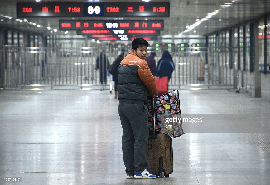 A Chinese man stands with his luggage at the Beijing west railway station in Beijing on December 26, 2012