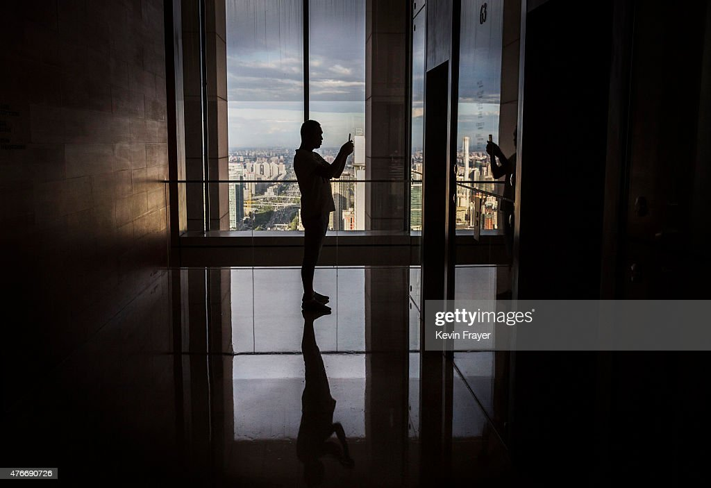 A Chinese man takes a picture of himself in a mirror as he wait s for the elevator in a luxury hotel on June 11, 2015 in Beijing, China. The area is the financial centre of China's capital city.