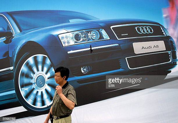 A Chinese man talks on his mobile phone beside a billboard advertising the German automaker's new Audi A8 in Beijing 28 July 2003 Sales of passenger...