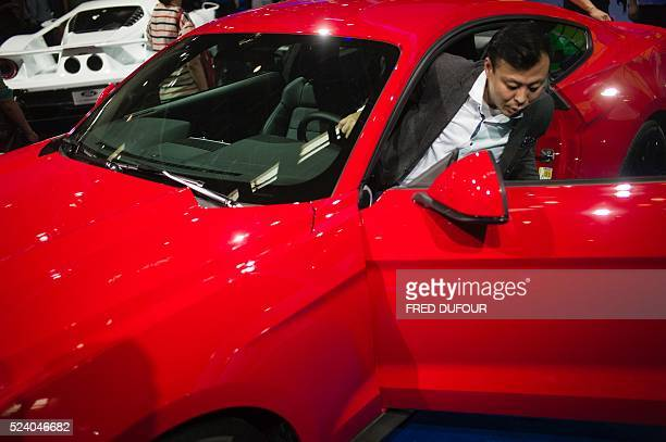 A Chinese man tries a Ford Mustang on display at the Beijing Auto Show in Beijing on April 25 2016 Global carmakers gathered in Beijing on April 25...