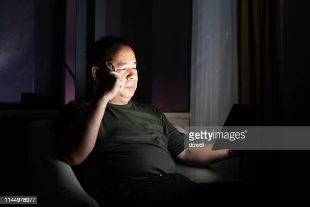 chinese man using digital tablet - un solo hombre fotografías e imágenes de stock