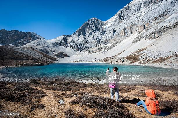 Chinese man using his smartphone take a picture of the Five colors lake at 4700m above sea level at Yading Nature Reserve Yading is located in...