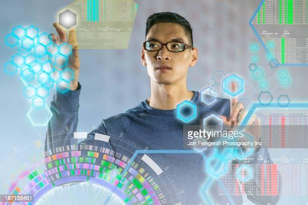 Chinese man using illuminated touch screen