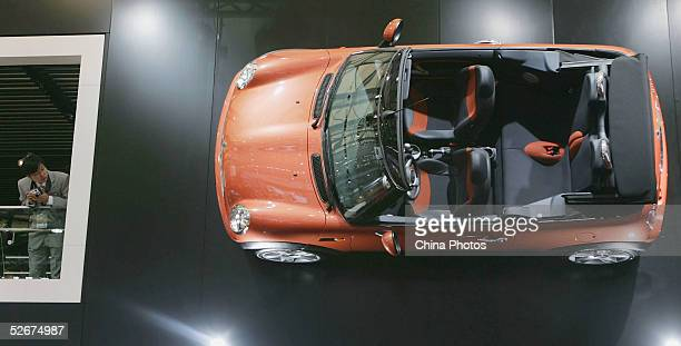 Chinese man views a Mini Cooper hung on the wall at the Auto Shanghai 2005 Exhibition on April 21, 2005 in Shanghai, China. Top world automakers will...