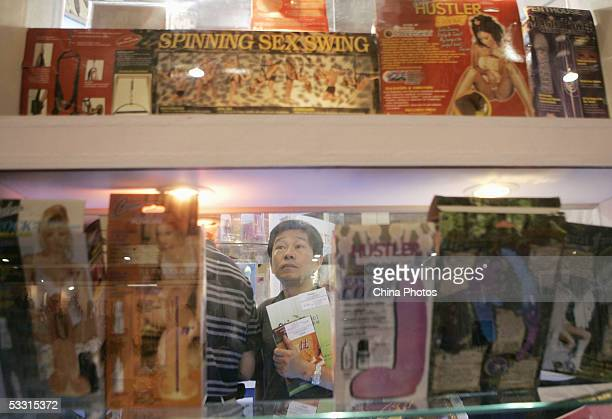 A Chinese man views sex toys at the AdultCare Expo at the International Exhibition Center on July 31 2005 in Shanghai China The expo featured the...