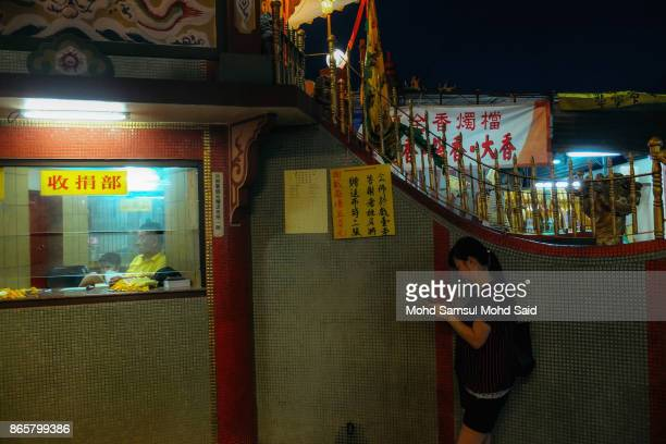 Chinese man waits for devotees to buy prayer paper during The Nine Emperor Gods Festival inside the temple on October 24 2017 in Kuala Lumpur...