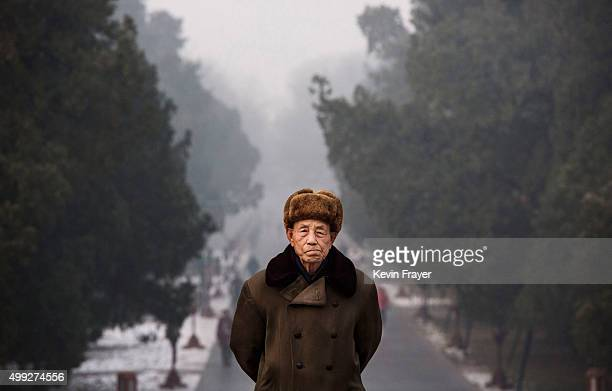 Chinese man walks at the Temple of Heaven park the Forbidden City shrouded in haze during a day of heavy pollution on November 30 2015 in Beijing...