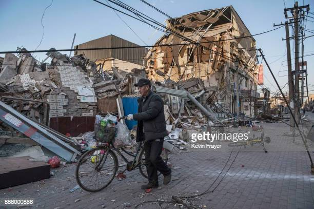 Chinese man walks by buildings demolished by authorities in an area that used to have migrant housing and factories on December 6 2017 in the Daxing...