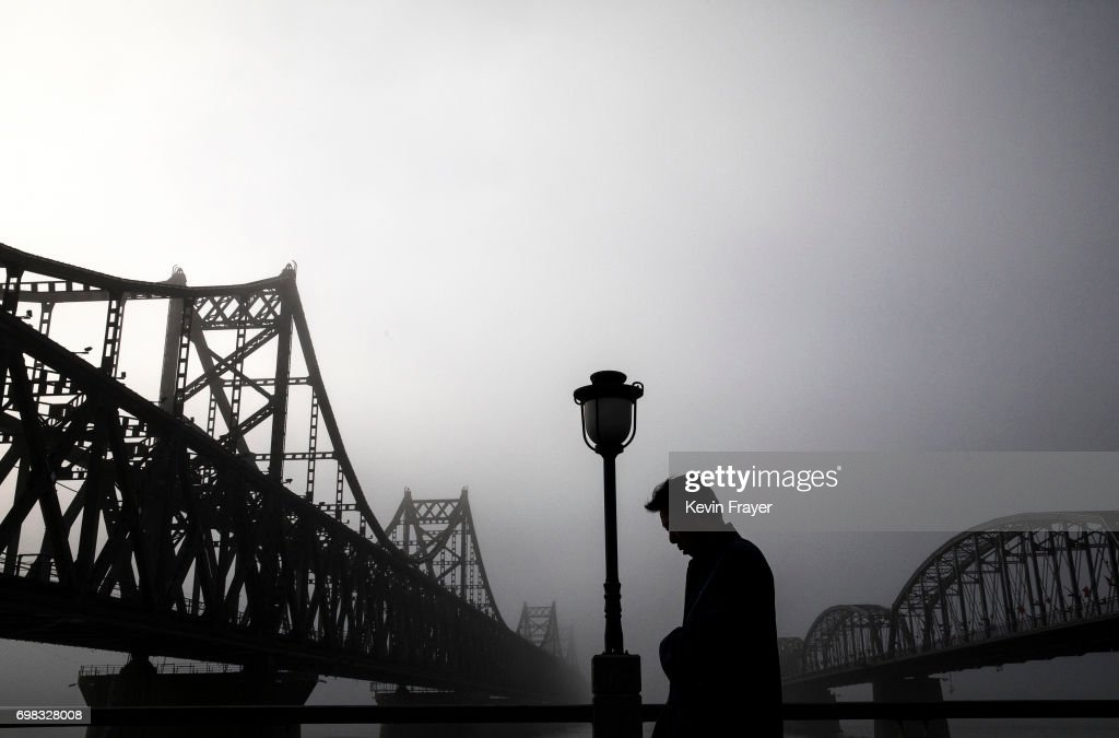 A Chinese man walks in the rain between 'Friendship Bridge', left, and 'Broken Bridge', right, as he looks across the Yalu river from the border city of Dandong, Liaoning province, northern China towards the city of Sinuiju, North Korea on May 24, 2017 in Dandong, China. China has long been North Korea's main ally and trading partner, but relations are increasingly strained by continued missile testing and provocations by the regime of Kim Jong Un. The North is almost entirely dependent on trade with China to feeds its impoverished economy, yet it has ignored calls by the international community to halt its nuclear and ballistic missile weapons programs. At least three-quarters of trade between the two nations flows through points along its 880-mile long shared border, a divide that reveals stark contrasts in development. Cities such as Dandong boast high-rise buildings and advanced infrastructure, and the Friendship Bridge serves as the conduit for the bulk of trade. From hired boats along the Yalu river, Chinese tourists peer into the reclusive North, marked by soldiers, meagre villages, and depleted farmland. The United States has pressured China to do more to leverage its clout with North Korea, though Beijing remains concerned that outright regime collapse in Pyongyang could trigger a rush of refugees across the border.