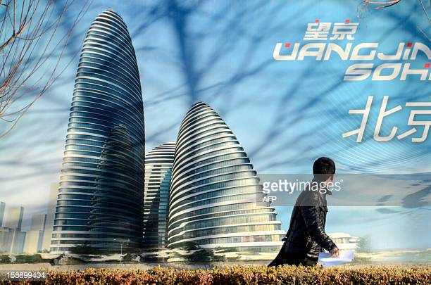 A Chinese man walks past a billboard illustrating the Wang Jing SOHO complex by renowned architect Zaha Hadid in Beijing on January 3 2013 Already...