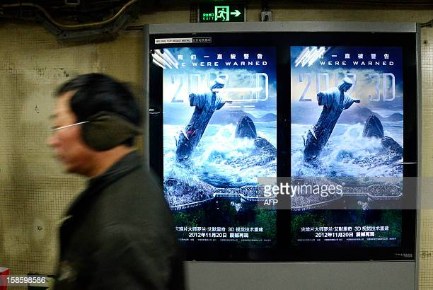 A Chinese man walks past a poster for the Hollywood disaster movie '2012' at a subway station in Beijing on December 20 2012 China has arrested...