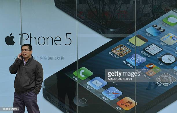 A Chinese man walks past an advertisement for an IPhone outside an Apple reseller in Beijing on March 18 2013 Apple was recently targeted over its...