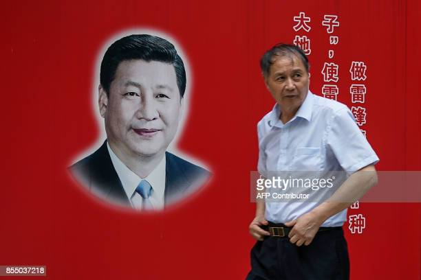 A Chinese man walks past the poster bearing the photo of the Chinese President Xi Jinping in Shanghai on September 28 2017 China celebrates its...