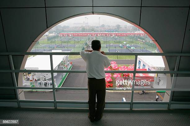 Chinese man watches tennis players practising at Beijing Tennis Center on September 16 2005 in Beijing China The twoweek long China Open is playing...