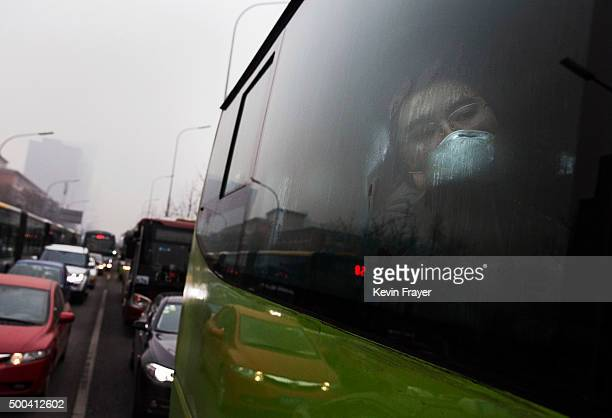 Chinese man wear sa mask to protect against pollution as he rides in a bus while commuting to work in heavy smog on December 8 2015 in Beijing China...
