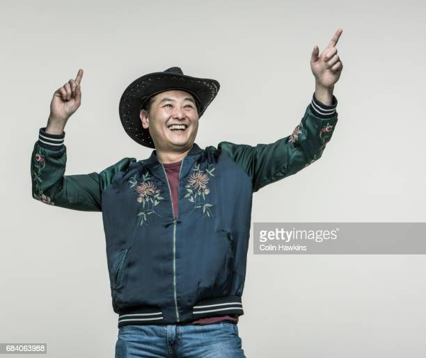 chinese man wearing cowboy hat - colin hawkins stock pictures, royalty-free photos & images
