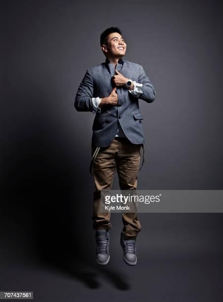 Chinese man wearing jacket and jumping