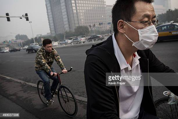 Chinese man wears a mask as he rides his bike during a polluted morning on October 17 2015 in Beijing China As a result of industry the use of coal...