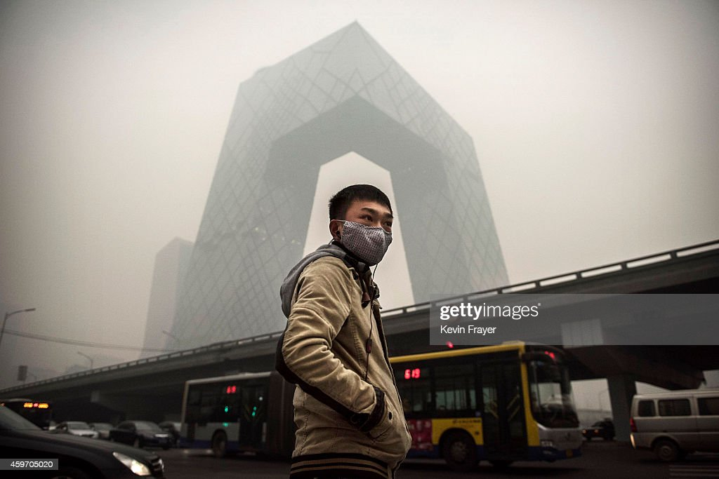 A Chinese man wears a mask as he waits to cross the road near the CCTV building during heavy smog on November 29, 2014 in Beijing, China. United States President Barack Obama and China's president Xi Jinping agreed on a plan to limit carbon emissions by their countries, which are the world's two biggest polluters, at a summit in Beijing earlier this month.