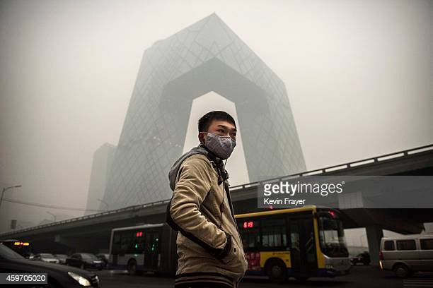 Chinese man wears a mask as he waits to cross the road near the CCTV building during heavy smog on November 29, 2014 in Beijing, China. United States...