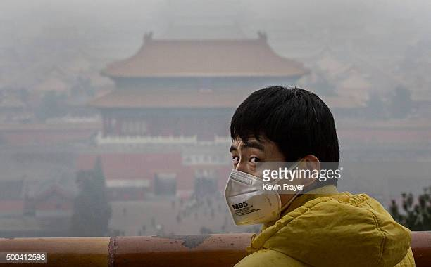 Chinese man wears a mask to protect against pollution as he visits Jingshan Park overlooking the Forbidden City in heavy smog on December 8 2015 in...