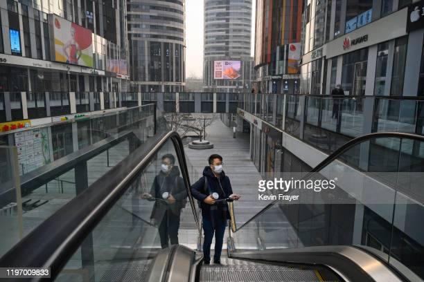 Chinese man wears a protective mask as he rides an escalator at a large empty shopping area that would usually be busy during the Chinese New Year...
