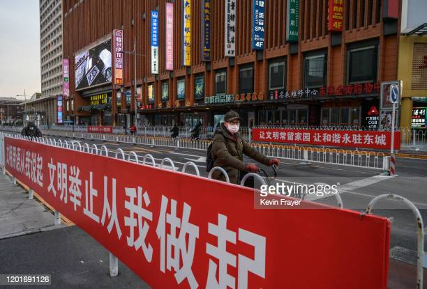 Chinese man wears a protective mask as he rides by a propaganda poster on a commercial street on February 18 2020 in Beijing China Apple said Monday...