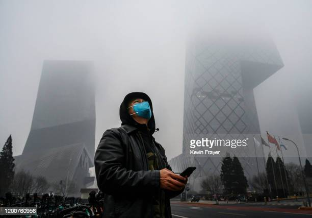 Chinese man wears a protective mask as he stands near the CCTV building in fog and pollution during rush hour in the central business district on...
